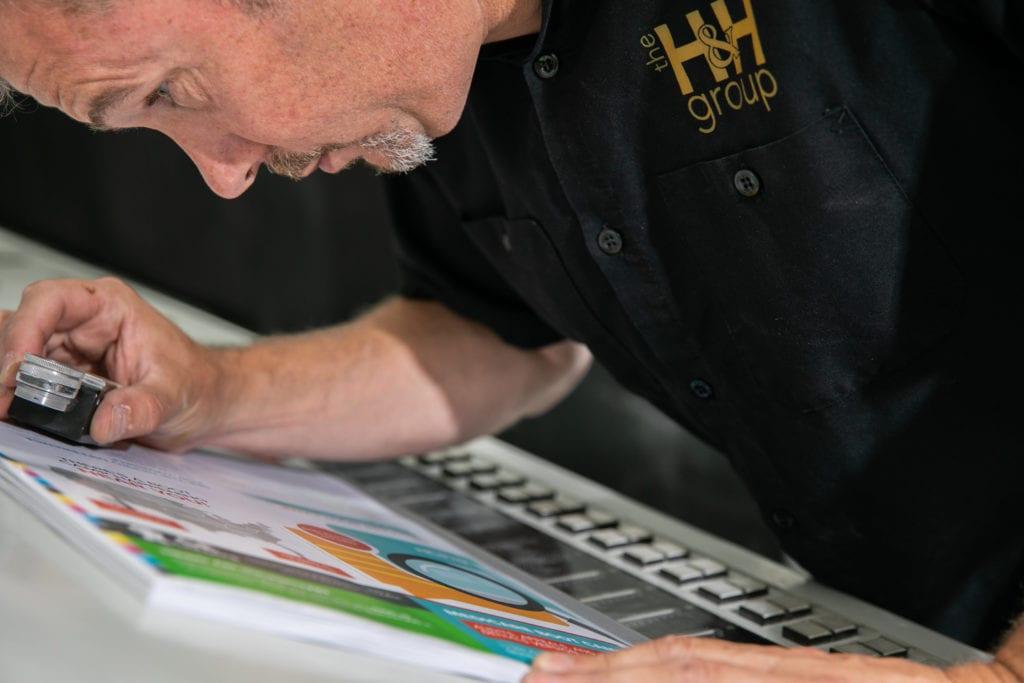 Man looking at print through magnifying glass