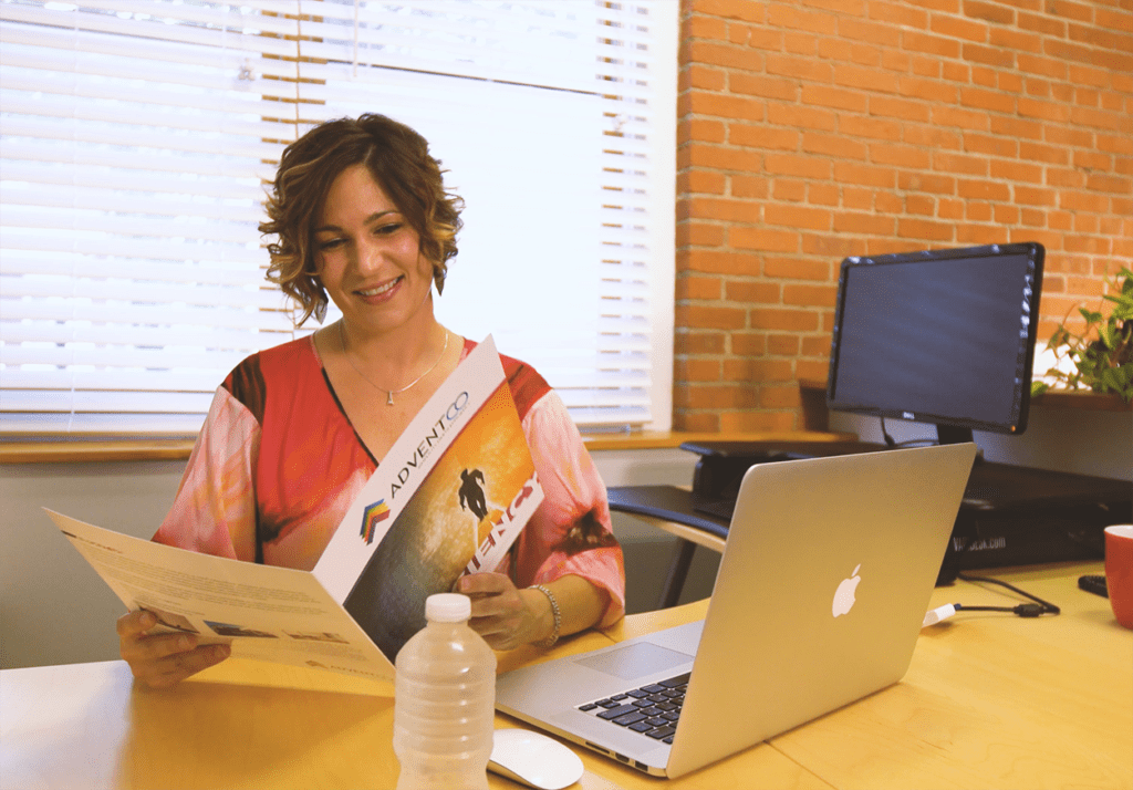 woman reading brochure at desk
