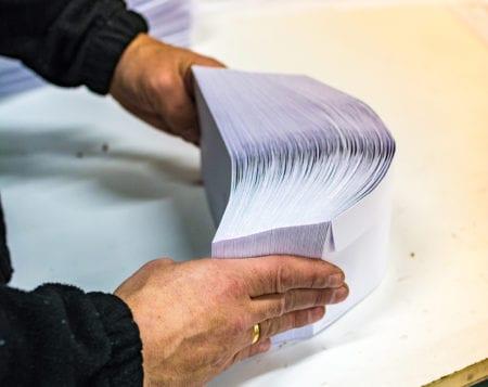 man manipulating envelopes for mailing